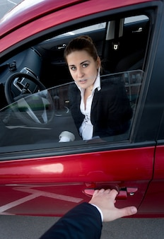Cambrioleur essayant de s'introduire dans la voiture. femme effrayée bloquant la porte
