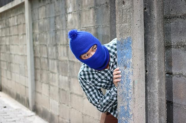 Un cambrioleur masqué se faufiler derrière un poteau de béton avant le cambriolage