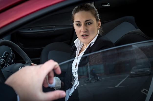 Un cambrioleur menace une jeune femme d'affaires assise dans une voiture