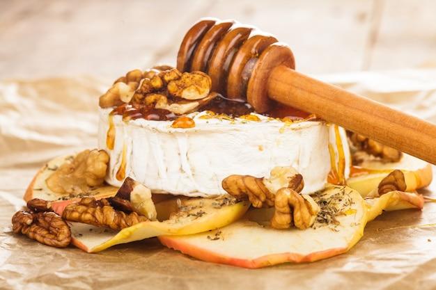 Camembert au four avec des pommes trempées dans du miel et des noix