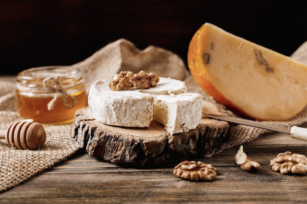Camembert aux noix et au miel sur une planche de bois