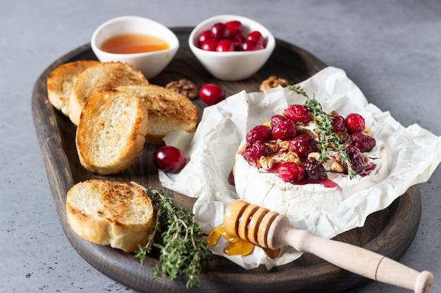 Camembert cuit au four avec canneberges, noix, miel et thym