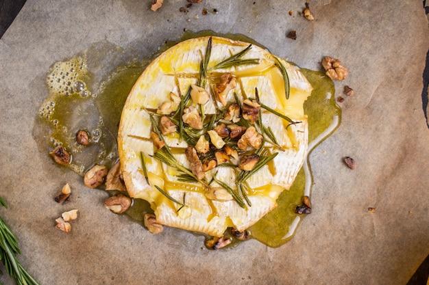 Camembert cuit au four délicieux avec du miel, des noix, des herbes et des poires