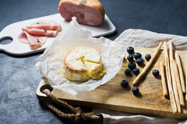 Camembert cuit au four avec myrtilles et jambon.