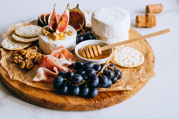 Camembert, figues, jamon, miel et raisins. assiette de fromage sur fond de marbre