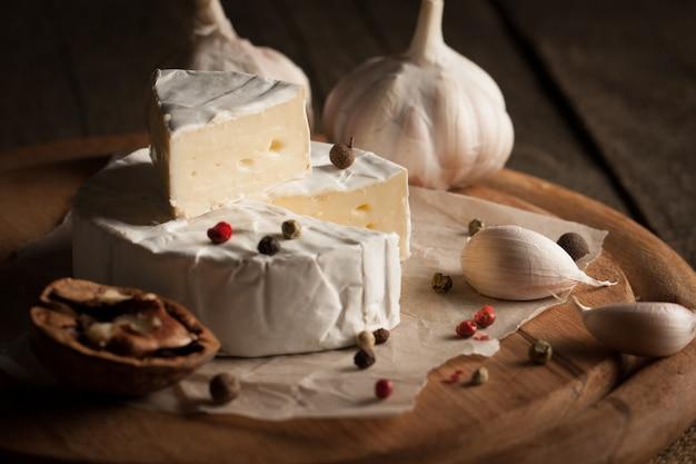Camembert et fromage brie sur bois avec tomates, laitue et ail. nourriture italienne. les produits laitiers.