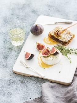 Camembert ou fromage brie avec figues fraîches, nid d'abeille et verre de vin blanc sur une planche de service sur gris rustique grunge