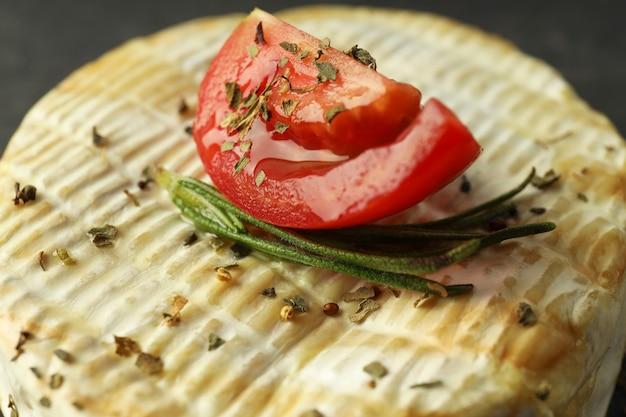 Camembert grillé avec tomate, romarin et épices, gros plan.