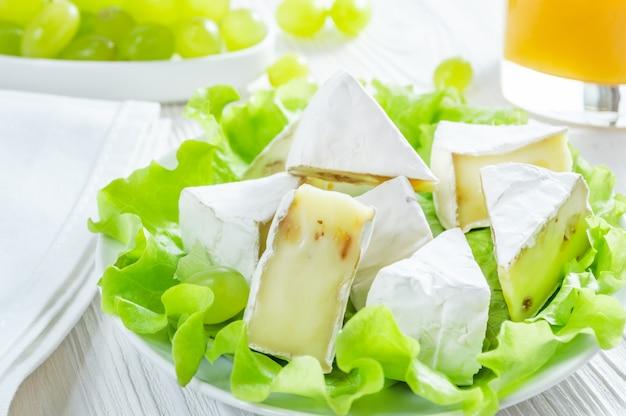 Camembert, raisins verts et verre de jus d'orange sur une table en bois blanche.