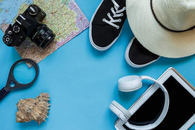 Caméra d'accessoires de voyage, chapeau de paille, carte, chaussures sur une disposition de vue de dessus plat fond bleu avec espace de copie