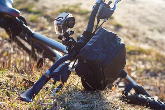 Caméra d'action sur un vélo avec un sac de vélo dans un étui étanche sur fond de nature.