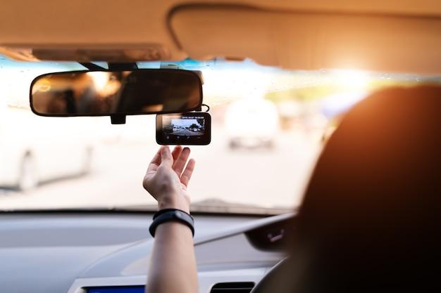 Caméra avant de voiture, enregistreur vidéo de jeu de femme à côté d'un rétroviseur