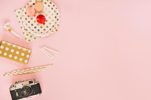 Caméra et cadeau près des trucs de fête et des macarons
