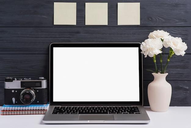 Caméra; cahier à spirale; vase à fleur et un ordinateur portable blanc ouvert blanc sur le bureau sur fond en bois