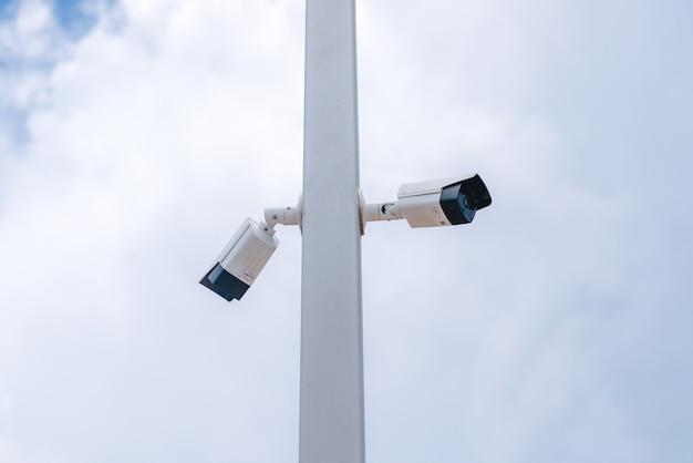 Caméra en circuit fermé montée sur un poteau avec la toile de fond du ciel bleu.