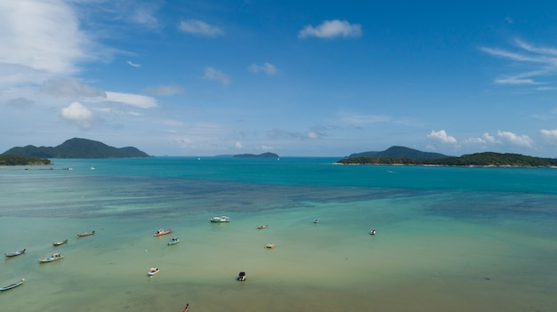 Caméra de drone de vue aérienne de haut en bas de la belle mer turquoise aux eaux claires avec des bateaux de pêche à longue queue et des voiliers en mer d'été île tropicale de phuket au sud de la thaïlande.