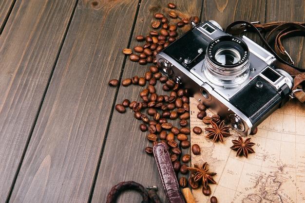 Caméra, grains de café, cannelle et autres espèces se trouvent sur la vieille carte en bois