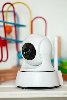 Caméra ip sur l'étagère avec des jouets, servant de moniteur pour bébé
