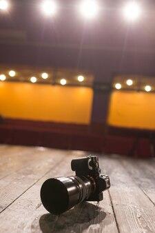 La caméra sur le parquet sur scène avec lampes et projecteurs