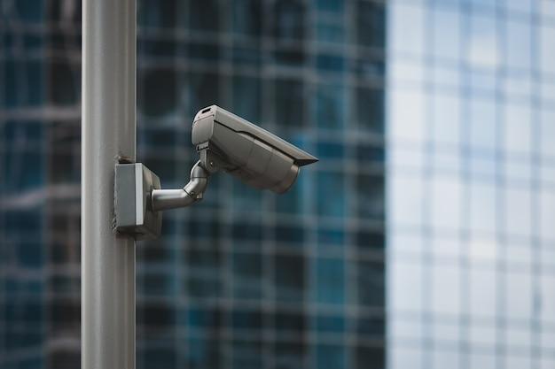 Caméra de sécurité externe sur poteau devant le mur du bâtiment en verre