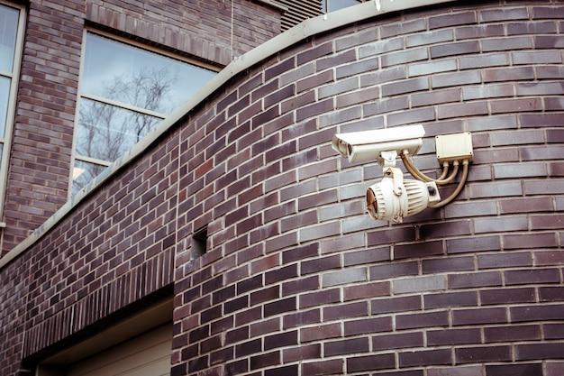 Caméra de sécurité sur le mur de briques du bâtiment