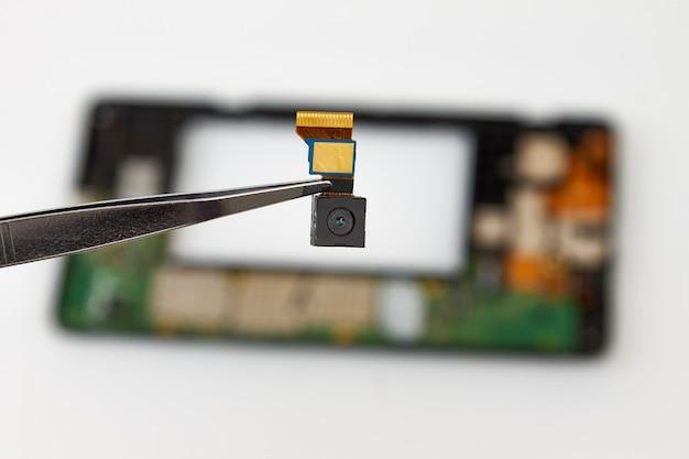 Caméra smartphone sur fond de téléphone démonté. service de réparation d'équipement numérique