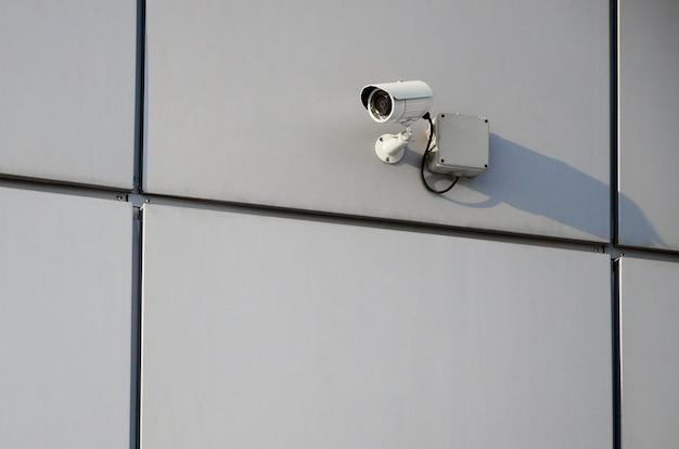 Caméra de surveillance blanche intégrée au mur de métal de l'immeuble de bureaux