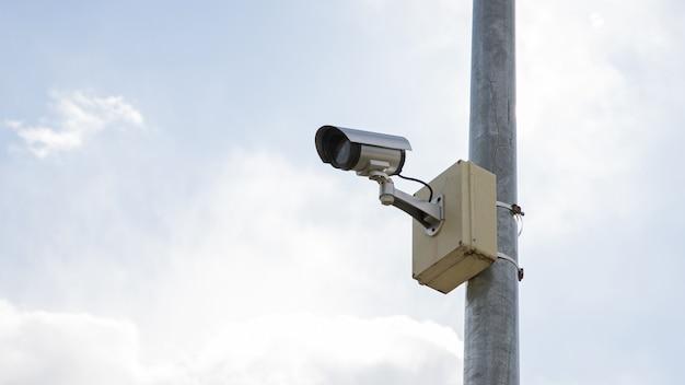 Caméra de surveillance montée sur un poteau avec fond de ciel.