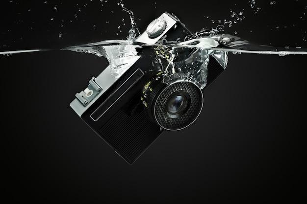 La caméra tombe dans l'eau, éclabousse et gouttes volumétriques sur fond noir. tir sous-marin.