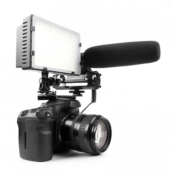 Caméra vidéo dslr isolée sur une surface blanche avec microphone et lumière.