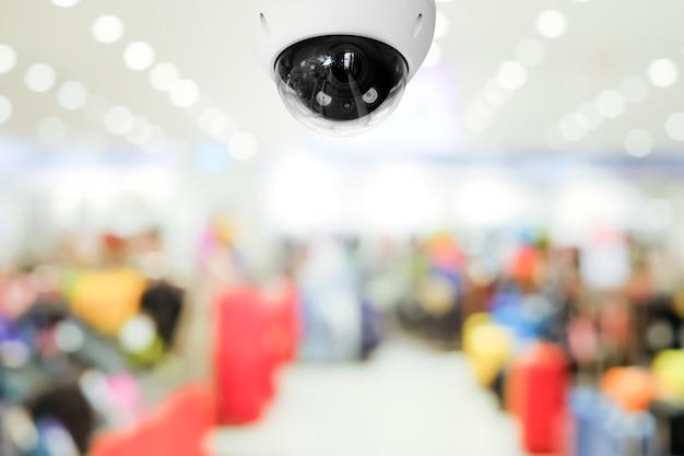 Caméra de vidéosurveillance publique moderne avec arrière-plan flou du centre commercial intérieur et espace de copie.