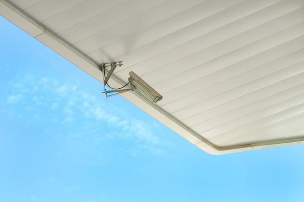 Caméra de vidéosurveillance sur un toit blanc, dans le ciel.