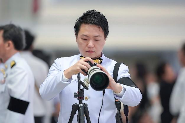 Caméraman professionnel tenant l'appareil photo sans miroir avec téléobjectif devant l'arrière-plan flou de la foule.