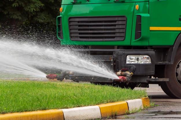 Le camion arrose de l'eau sur l'herbe verte. services de garde en ville.