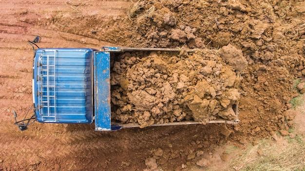 Un camion à benne basculante décharge le sol sur le chantier de construction. vue aérienne