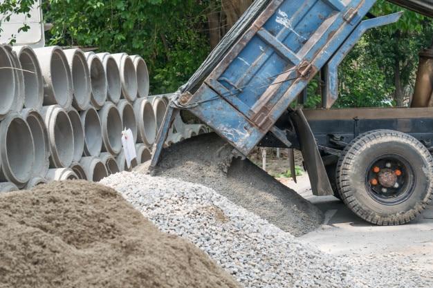 Camion à benne basculante déchargeant du sable sur le chantier de construction