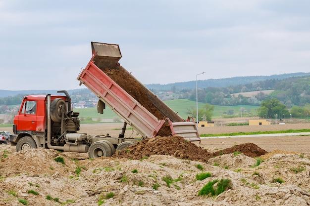 Camion à benne basculante déchargeant de la terre ou du sable sur un chantier de construction.