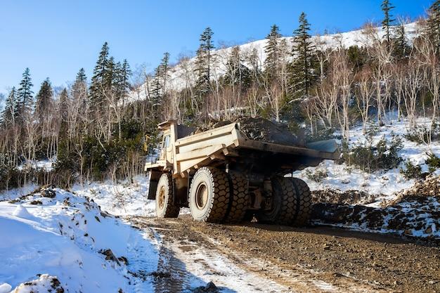 Camion à benne basculante avec du minerai dans la mine d'or