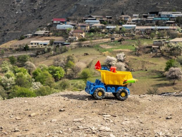 Camion à benne basculante sale jaune jouet sur le fond d'un paysage de montagne.