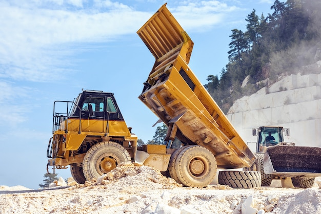Camion à benne basculante travaillant avec une excavatrice