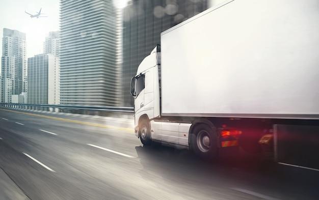 Camion blanc se déplaçant rapidement sur l'autoroute avec une ville moderne