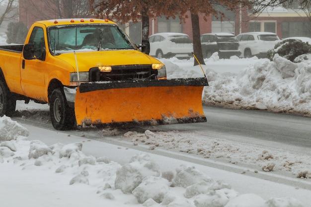 Un camion chasse-neige dégage une route après le blizzard de tempête de neige blanchi par blanc pour l'accès des véhicules