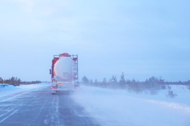 Un camion-citerne roule le long d'une route dans le nord en hiver
