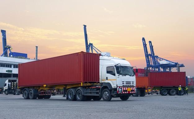 Camion conteneur rouge dans le port du navire logistique