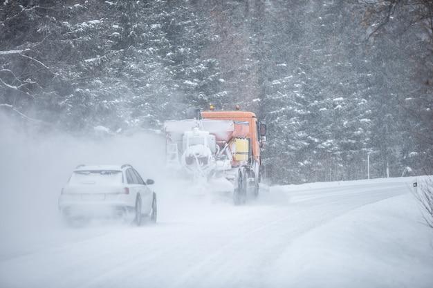 Un camion d'entretien routier à conduite à gauche dégage la neige de la route dans la forêt avec une voiture derrière elle.