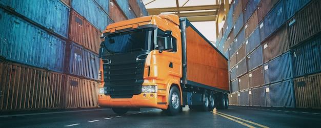 Le camion est dans le port et ont des conteneurs disposés à l'arrière.