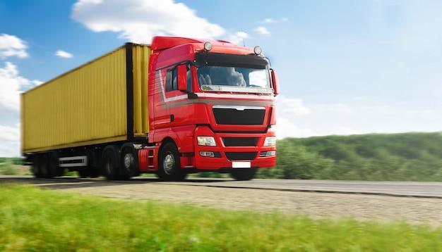 Camion européen avec conteneur sur autoroute et ciel bleu avec des nuages.