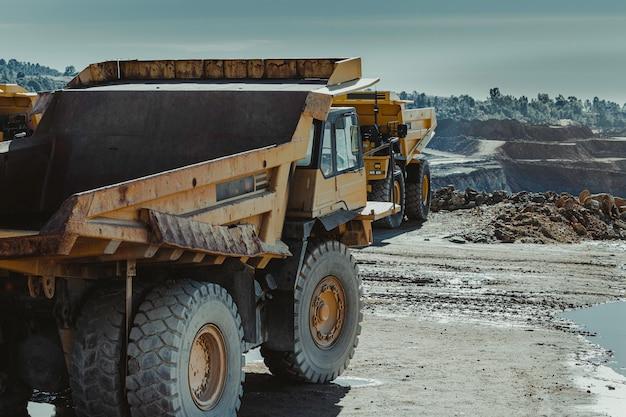 Camion jaune par derrière et un autre devant avec les mines