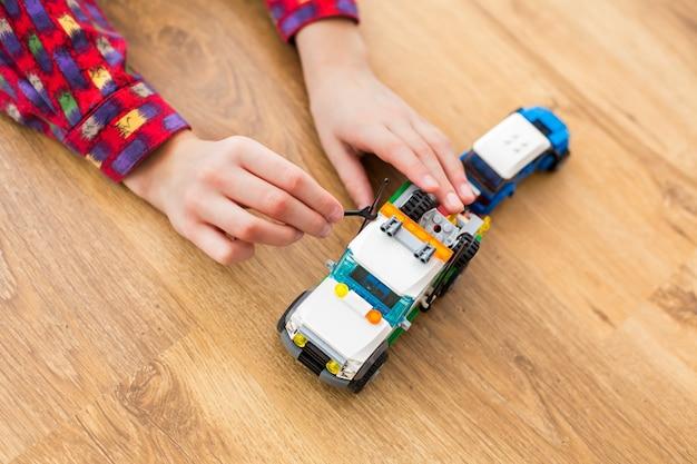 Camion jouet fixant la main du garçon. enfant utilisant une petite clé à molette. réparation de l'antenne. doit avoir une radio opérationnelle.