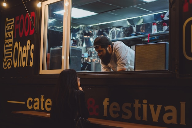 Camion de nourriture avec des hot-dogs et des hamburgers. chef barbu brutal